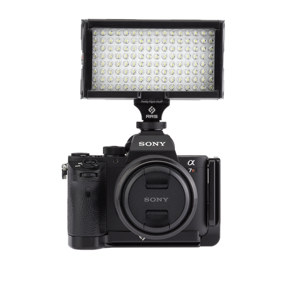 Camera with hot shoe adapter and SNAP QR Adapter on top - connected to video light